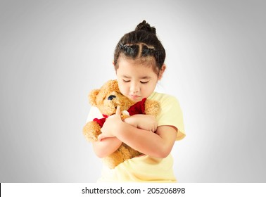 Sad asia Little girl hugging teddy bear alone, studio shoot - Shutterstock ID 205206898