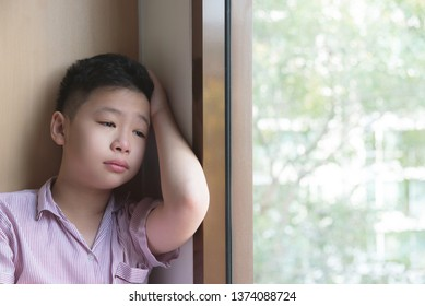 Sad asian boy sitting near by the window at home and looking out