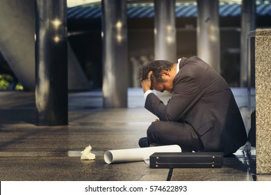 Sad Asian businessman losing job, depressed employee people who's employment. Alcoholic Entrepreneur sit on floor with anxiety, upset, worried, stressed and lonely after know rate of jobless is high.