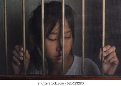 sad asian child standing behind the wire screen window in dark mood.  Unhappy kid alone at home. Upset.