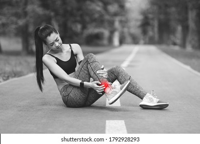 Sad Asian Girl Having Ankle Pain After Jogging In Park, Massaging Red Sore Spot, Sitting On Path, BW Style With Free Space