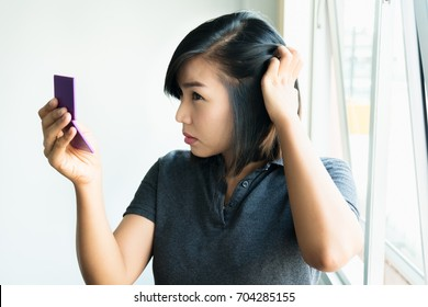 Sad asian girl looking at her damaged hair, Postpartum hair loss condition
