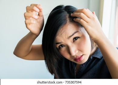 Sad asian girl looking at her damaged hair, Postpartum hair loss condition