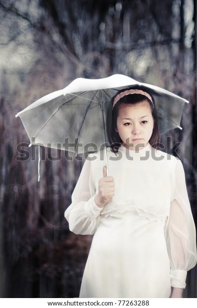 Sad asian girl standing under the rain with umbrella