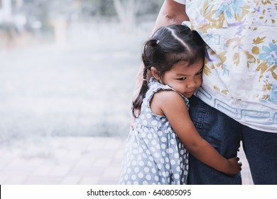 Sad asian little girl hugging her mother leg in vintage color tone