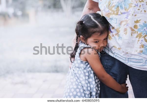 悲傷的亞洲小女孩擁抱她母腿復古色調