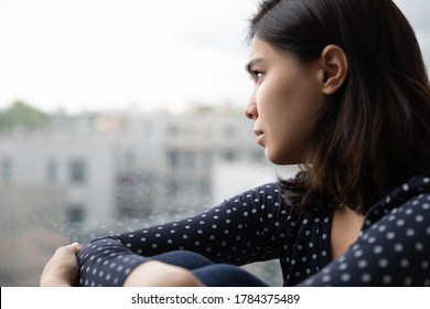 Sad Asian millennial girl look in window distance thinking or pondering alone at home, thoughtful upset unhappy Vietnamese woman lost in thoughts dreaming, feel lonely distressed, loneliness concept
