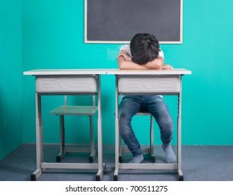 Sad Asian school boy sitting in classroom
