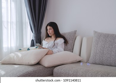 sad asian woman looking out side and using smartphone, cellphone on sofa at living room. concept of young woman broken heart.