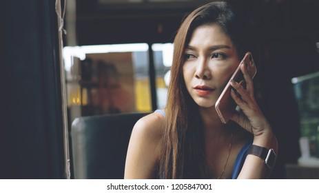 Sad Asian women breakup with boyfriend by mobile phone