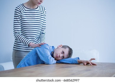 Sad autistic boy lying on a table and his mother standing next to him
