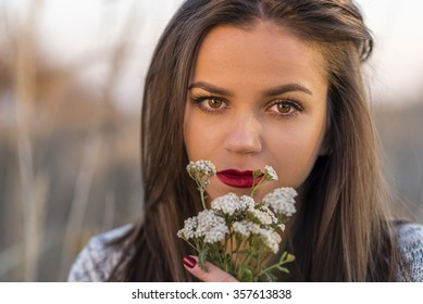 Sad autumn look. Portrait of a nice teenager girl holding small bouquet in a autumn field. Girl has brown eyes and hair and red lips.