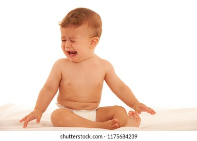Sad baby boy in crying on bed isolated over white