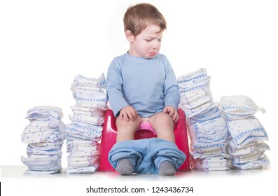 Sad baby boy sitting on chamber pot because he must stop using diapers. Potty training concept