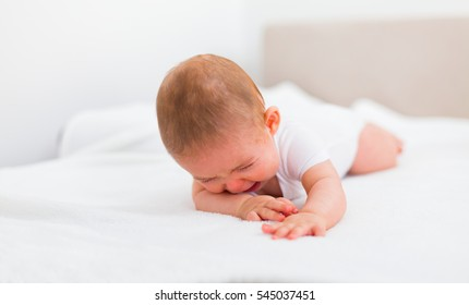 Sad baby crying on bed alone at home.