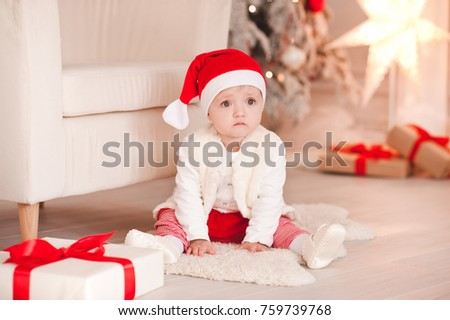 sad baby girl 1 year old wearng santa claus hat sitting on floor over christmas background