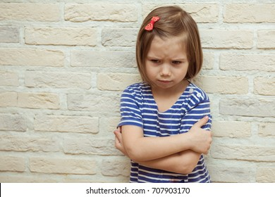 Sad baby girl against a brick wall. The concept of education, relationships, childhood fears