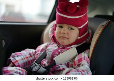 sad baby girl in car seat in winter time
