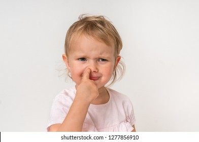 Sad baby girl is picking her nose with finger inside - hygiene concept