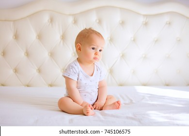 sad baby in white sunny bedroom.