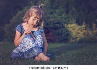 Sad barefoot girl dressed in blue dress sitting on grass and holding her small harmonica