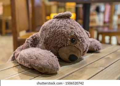 Sad bear doll lay down on wooden table