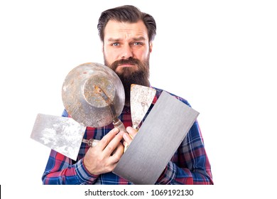 Sad bearded man holding used masonry tools
