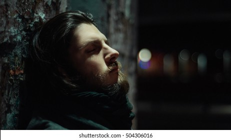 sad, bearded young man looking thoughtfully into the distance standing at night under the bridge