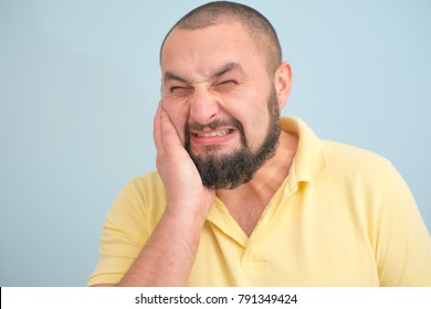 Sad bearded young man standing and having toothache