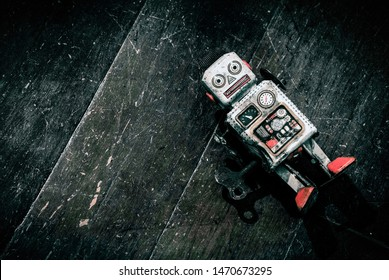 sad beat up old retro robot on a wooden floor shot from above