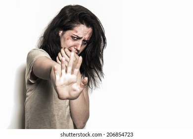 Sad beaten up girl with wounds on the face being scared and asking to stop