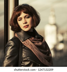 Sad beautiful fashion woman on city street Stylish female model with bob hair wearing black leather coat and brown scarf