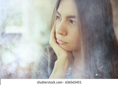 Sad beautiful girl sitting in a cafe alone at a table