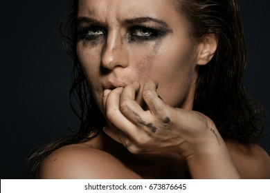 Sad and beautiful woman with smudged makeup on her face