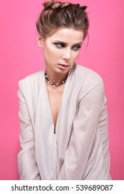 Sad beautiful young woman on pink background. Gentle female image, the hair and makeup. Necklace with beads on neck