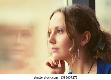 Sad beautiful young woman with ponytal hairstyle looking through window