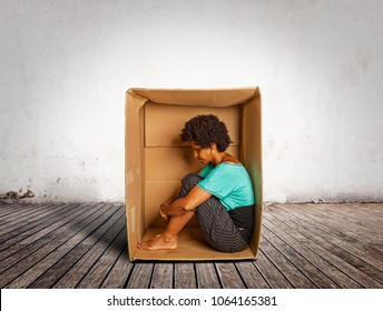 sad black woman inside a Box on a room