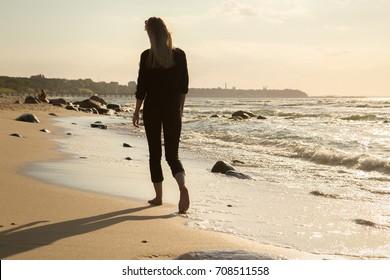 sad blond barefoot woman walking away at sunny sea beach, toned image