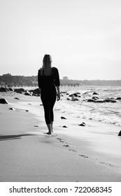 sad blond barefoot woman walking away at sunny sea beach, monochrome image