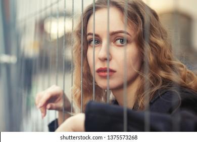 sad blond girl behind bars looking at camera