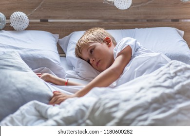 Sad blond hair boy lying in his bed