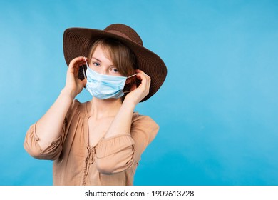 Sad blonde caucasian girl in brown summer hat, beige shirt and medical mask looking to the camera, standing on a blue background with empty space for advertisement. Coronavirus in tourism concept