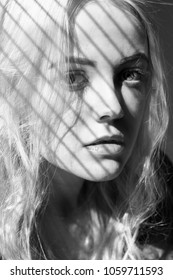 sad blonde woman in sun light with blinds shadow looking at camera monochrome