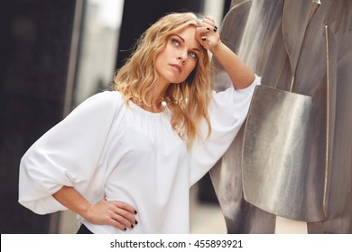 Sad blonde woman in white blouse leaning on steel figures