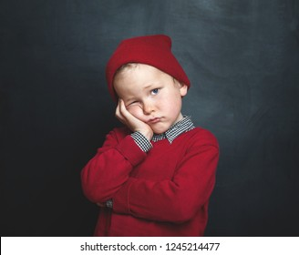 Sad and bored child with hand on head. Upset toddler boy. problem and sick child. concept for bullying, depression tired stress or frustration. Waiting parents day at school. Against school blackboard