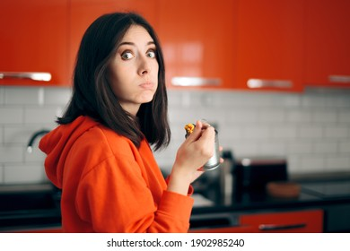 Sad Bored Woman Eating From a Can in the Kitchen. Young person unable to cook eating canned food