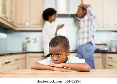 Sad boy against parents arguing in the kitchen