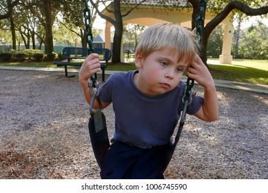 Sad boy alone on a playground swing