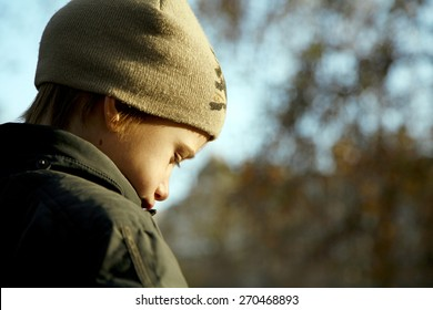Sad boy in autumn warm clothes outdoors