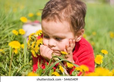 Sad boy with a bouquet of dandelions